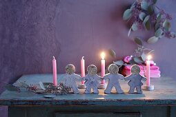 Lit candles behind festive paper doll chain moulded from concrete