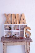 Festive arrangement with cardboard letters spelling XMAS