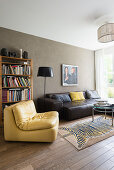 Yellow leather easy chair and black leather couch in front of bookcase in living room with olive-green wall