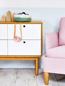 Spielzeugkamera hängt an Kommode mit weißen Schubladen