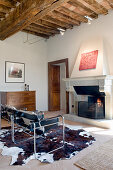 Classic chairs on cowhide rug in front of fireplace