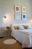 Double bed and modern artwork in simple bedroom