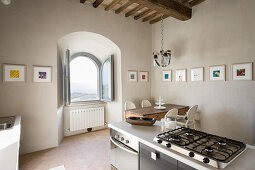 Open window and gallery of pictures on walls in kitchen of renovated château