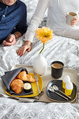 Croissants, eggs, coffee and yellow poppy on breakfast tray on bed with couple in background