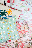 Colourful scatter cushions on bed in child's bedroom