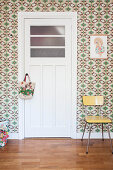 White interior door in room with retro wallpaper