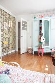 Girl in front of mint-green wardrobe with mirrored door in child's bedroom with retro wallpaper