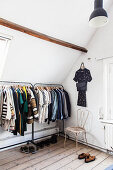 Clothes rail in attic room with wooden floorboards
