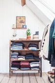 Folded clothing on open-fronted shelves and clothes rail in attic room with wooden floorboards