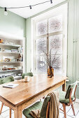 Table and chairs in front of window in dining area with green walls