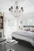 Chandelier in the elegant bedroom in gray and white