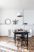 Dark dining table and designer chairs in front of white wall