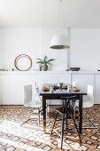 Dunkler Esstisch mit Designerstühlen vor weißer Wand