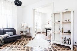 Tierfellteppich auf gemustertem Fliesenboden, Vitrinenschrank, graues Sofa und Vintage Servicewagen im Wohnzimmer mit Durchgang