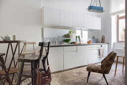 White kitchen counter, upholstered chair and bistro table with barstools in kitchen