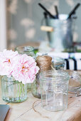 Preserving jars and pink flowers on wooden table