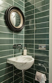 Green wall tiles, marble sink and mirror in guest toilet