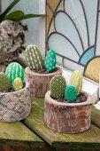 Decorative arrangement of pebbles painted to resemble cacti in pots