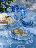 Table set with blue-patterned crockery and tarts