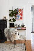 Fur blanket on swivel chair in front of houseplant on console table