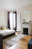 Open fireplace and stucco ceiling in black and white bedroom