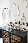 Various mirrors on wall above chest of drawers in bathroom