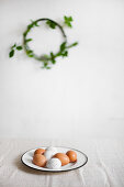 Brown eggs and white, speckled eggs on enamel plate with wreath of leafy branches in blurred background