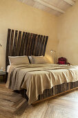 Double bed with headboard made from reclaimed wood in bedroom