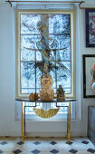 Buddhafigur auf einem Konsolentisch vor dem Fenster mit bemaltem Rollo
