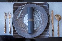 Goldenes Besteck um runden Teller und eckigen Platzteller in Grautönen