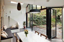 Corner bench and open terrace doors leading into garden in dining room