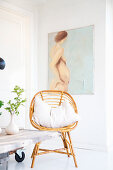 Rattan chair with cushions in front of nude artwork