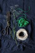 Naturgarn, Vintage Schere, grüner Bindfaden auf blauem Stoff