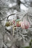 Vintage Christmas-tree decorations on frosty branch