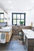 Badezimmer mit zwei Waschbecken, Fenster, Badewanne und grossformatigen Fliesen in Betonoptik