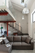 Grey couch in industrial loft apartment with gallery