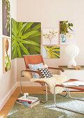 Ledersessel mit Tierfell, Kissen und Fusshocker im Zimmerecke mit Pflanzenbildern