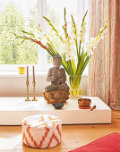 A statue of Buddha and gladioli on a pedestal in front of a window