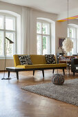 Yellow sofa and standard lamp in front of window in period apartment
