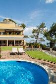 Pool und Liegen im Garten einer mediterraner Villa