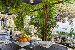 Gedeckter Tisch mit Zitrusfrüchten unter begrünter Pergola, mit Blick auf das Meer