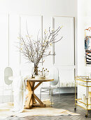 Round wooden designer table and white designer metal chairs on animal fur rug