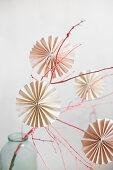 Papierrosetten an einem rosafarben bemalten Zweig