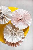 Blassrosafarbene Papierrosetten auf einem gelben Hocker