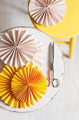 Rosafarbene und gelbe Papierrosetten auf zwei Hockern