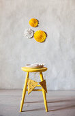 Paper rosettes on wall above yellow stool with bunting