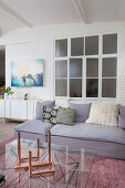 Grey corner sofa with scatter cushions and coffee table with glass top in front of interior doors with glass panels