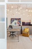 Blick ins Arbeitszimmer mit Schreibtisch, Drehstuhl, Sessel und Designerleuchten