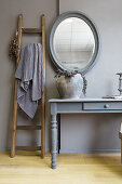 Ladder next to console table in elegant, rustic interior