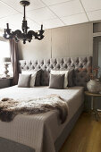 Bed with button-tufted headboard in small bedroom in shades of grey
